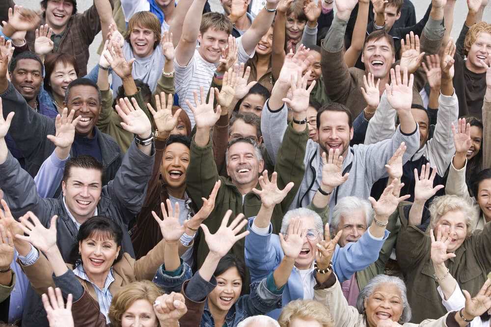 a crowd of people are raising their hands for employee engagement training
