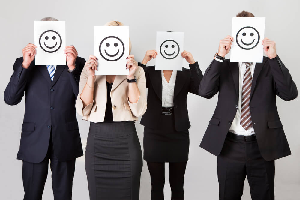 4 people hold up smiley faces to show how managers can better engage their teams