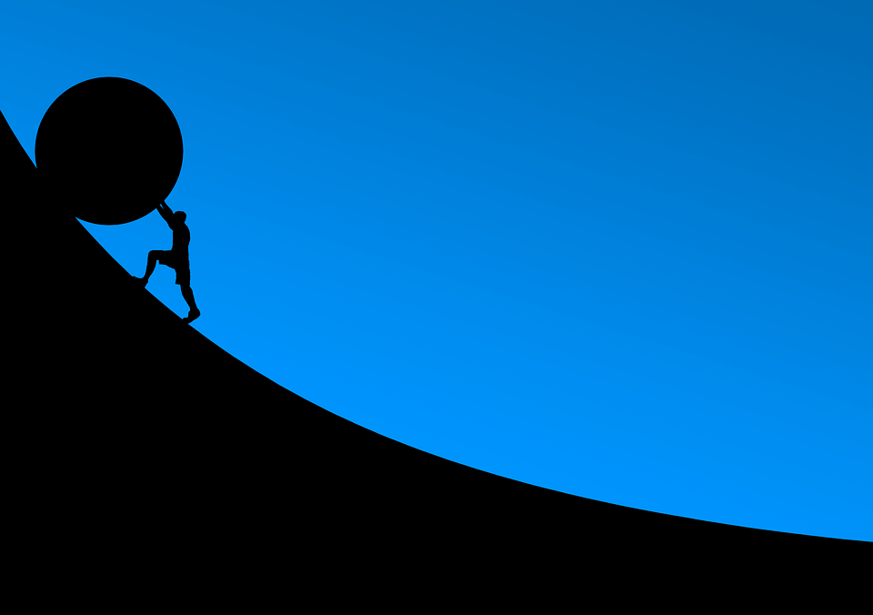rolling a stone uphill to show the struggle to follow up on employee engagement surveys