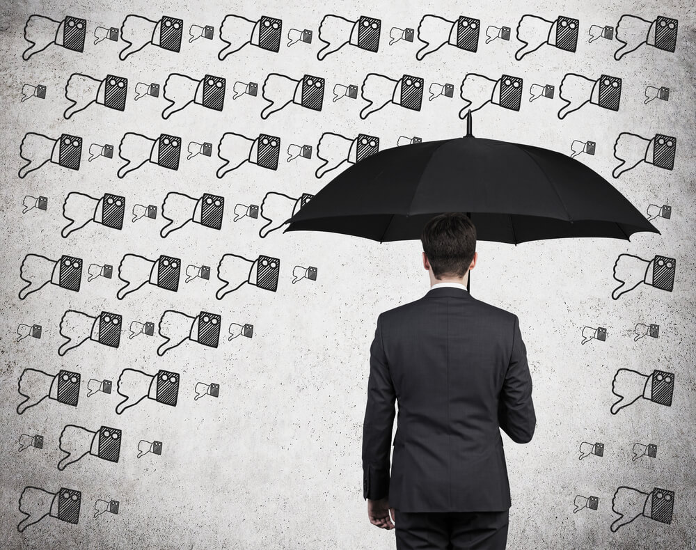A man with an umbrella is protected from hundreds of thumbs-down signs